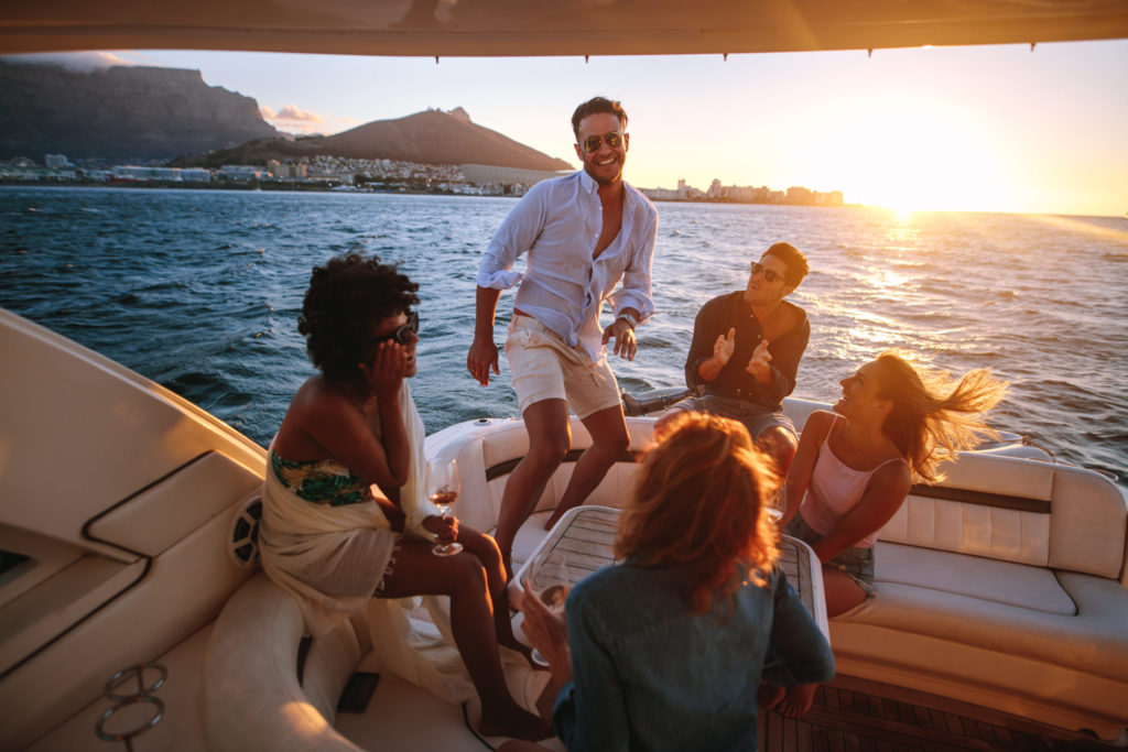 Blog - Group of young people dancing in boat party. Multiracial friends having fun in sunset yacht party.